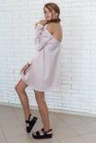Beautiful woman in elegant beige fashionable dress posing in studio Royalty Free Stock Images