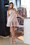 Beautiful woman in elegant beige fashionable dress posing in studio Royalty Free Stock Photos