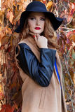 Beautiful woman in elegant black hat with large fields and bright red lipstick on her lips in a coat walks in the park near Royalty Free Stock Photo