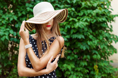 Beautiful woman in elegant hat with red lips and black polka-dot dress Royalty Free Stock Photos