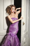 Beautiful sexy woman in elegant purple dress. Beautiful woman in elegant dress standing at the white door Royalty Free Stock Photos