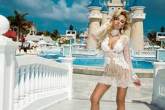 Beautiful woman in an elegant evening gown, stands against the background of a fountain and palace in the Caribbean. Beautiful sexy woman girl in an elegant royalty free stock photos
