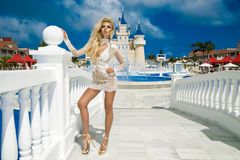 Beautiful woman in an elegant evening gown, stands against the background of a fountain and palace in the Caribbean. Beautiful sexy woman girl in an elegant stock photography