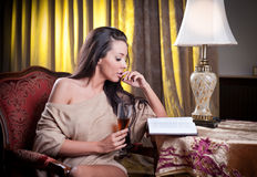 Beautiful sexy woman with glass of wine reading a book sitting on chair Royalty Free Stock Photography