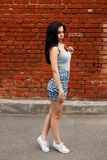 Beautiful woman in a gray T-shirt and summer skirt. With sneakers near a red brick wall stock images