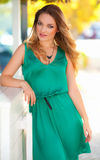 Beautiful woman with green dress and blond hair outdoor. Fashion girl Stock Images