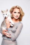 Beautiful sexy woman hug pets dog makeup dress blond Royalty Free Stock Image