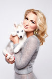 Beautiful sexy woman hug pets dog makeup dress blond. Beautiful young sexy blonde with beautiful make-up natural beauty dressed in fashionable stylish evening Stock Photography