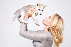 Beautiful sexy woman hug pets dog makeup dress blond. Beautiful young sexy blonde with beautiful make-up natural beauty dressed in fashionable stylish evening Stock Photo