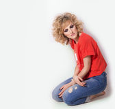 Beautiful sexy woman in jeans and a bright orange t-shirt is sitting on her knees on the floor in the Studio on a white background Stock Photo