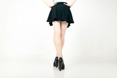 Beautiful sexy woman legs with black high heels and mini skirt Stock Photography