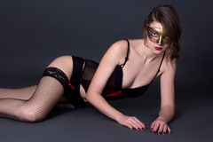 Beautiful sexy woman in lingerie and mask lying over grey Royalty Free Stock Image