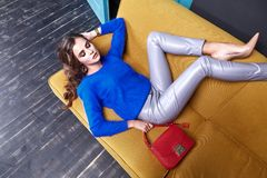 Beautiful sexy woman long brunet hair spring autumn collection f. Ashion clothes date party success business wear blue sweater lather pants shoes lie on sofa Royalty Free Stock Photo