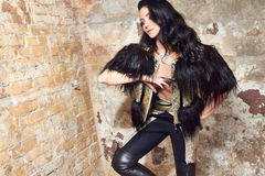 Beautiful sexy woman long brunette hair in black fur and Leather trousers near yellow and red brick wall on background in rock sty Royalty Free Stock Photography