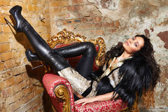 : Beautiful sexy woman long brunette hair in black fur Treads on high heel gold pans sitting on the chair red brick wall backgroun Royalty Free Stock Photography