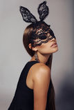 Beautiful woman with long dark hair in lace bunny mask stock photography