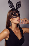 Beautiful woman with long dark hair in lace bunny mask royalty free stock photo