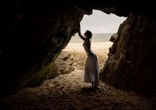 Beautiful and woman in long dress, stands and poses in a cave next to a sandy beach in Ireland. royalty free stock photos