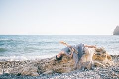 Beautiful woman in a long dress of voila lies on a big stone near the sea stock photo