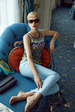 Beautiful sexy woman luxary dress jewelry make-up interior. Beautiful young sexy blond woman with short hair sunglasses  makeup business woman reading a rest in Stock Photos