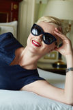 Beautiful sexy woman luxary dress jewelry make-up interior. Beautiful young sexy blond woman with short hair sunglasses  makeup business woman reading a rest in Royalty Free Stock Photo