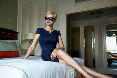 Beautiful sexy woman luxary dress jewelry make-up interior. Beautiful young sexy blond woman with short hair sunglasses  makeup business woman reading a rest in Royalty Free Stock Image