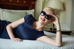 Beautiful sexy woman luxary dress jewelry make-up interior. Beautiful young sexy blond woman with short hair sunglasses  makeup business woman reading a rest in Stock Images