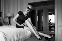 Beautiful sexy woman luxary dress jewelry make-up interior. Beautiful young sexy blond woman with short hair sunglasses  makeup business woman reading a rest in Royalty Free Stock Images