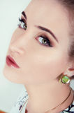 Beautiful sexy woman with natural day makeup wearing green earri Stock Photography
