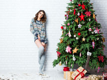 Beautiful sexy woman near a Christmas tree. Royalty Free Stock Images