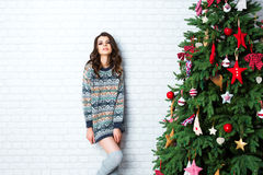 Beautiful sexy woman near a Christmas tree. Stock Photo