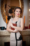Beautiful woman near a fireplace in vintage scenery. Portrait of girl in slim fit dress holding a book Stock Photos