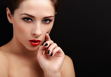 Beautiful sexy woman portrait. Black eyeliner, red lipstick and black nails polish. Looking with empty copy space background Royalty Free Stock Image