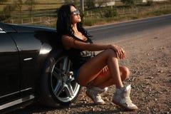 Beautiful sexy woman posing beside a car Royalty Free Stock Image