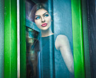 Beautiful woman posing in a green painted window frame, shot through window. gorgeous young female with long curly hair Royalty Free Stock Photo
