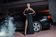 Beautiful sexy woman posing standing near car. Fashion portrait of beautiful sexy woman model girl posing standing near black car with bright makeup at night Royalty Free Stock Photo