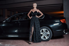 Beautiful sexy woman posing standing near car. Fashion portrait of beautiful sexy woman model girl posing standing near black car with bright makeup at night Stock Photography
