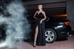 Beautiful sexy woman posing standing near car. Fashion portrait of beautiful sexy woman model girl posing standing near black car with bright makeup at night Stock Photos