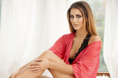 Beautiful and sexy woman in red bathrobe Stock Images