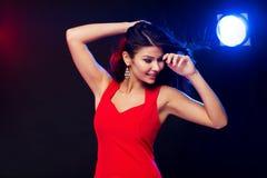 Beautiful sexy woman in red dancing at nightclub Stock Photo