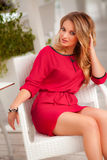 Beautiful woman with red dress and blond hair posing outdoor. Fashion girl Stock Images