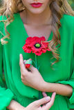 Beautiful sexy woman with red lips and bright make-up in a green dress with a poppy in his hands in a forest Royalty Free Stock Image