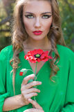 Beautiful woman with red lips and bright make-up in a green dress with a poppy in his hands in a forest Stock Photos