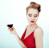 Beautiful sexy woman in red satin dress and red lips drinking vi Royalty Free Stock Photo