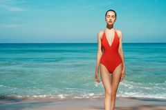 Beautiful sexy woman in red swimwear on the beach. Beautiful sexy lady on tropical beach. Fashionable woman with slim perfect figure walking in front of blue sea royalty free stock photos