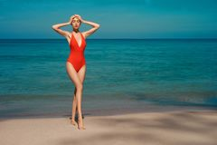 Beautiful sexy woman in red swimwear on the beach. Beautiful sexy lady on tropical beach. Fashionable woman with slim perfect figure walking in front of blue sea stock photos