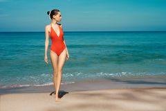 Beautiful sexy woman in red swimwear on the beach. Beautiful sexy lady on tropical beach. Fashionable woman with slim perfect figure walking in front of blue sea royalty free stock photo