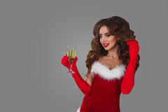 Beautiful woman in Santa Claus clothes with champagne glass over a grey background. Stock Photos