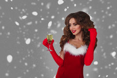 Beautiful woman in Santa Claus clothes with champagne glass over a grey background with snow. Stock Photos