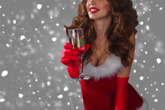 Beautiful woman in Santa Claus clothes with champagne glass over a grey background with snow. Royalty Free Stock Photos